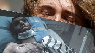 Egy nő egy bántalmazott férfi fotóját tartja az egyik minszki kórház előtt