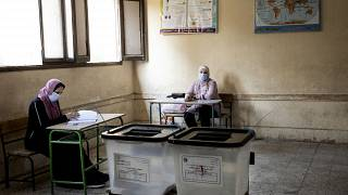 Election officials wait for people to vote on the first day of the Senate elections inside a polling station in Cairo, Egypt, Tuesday, Aug. 11, 2020
