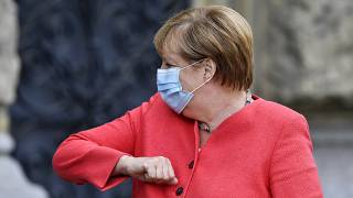 German chancellor Angela Merkel shows her elbow for a greeting in Duesseldorf, Germany, Tuesday, Aug. 18, 2020.