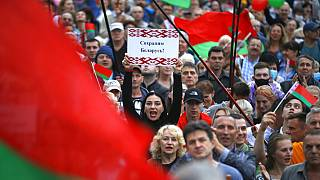 """""""Save Belarus!"""" reads the poster a woman is holding among demonstrators in Minsk"""