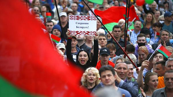 """Save Belarus!"" reads the poster a woman is holding among demonstrators in Minsk"