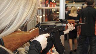 امرأة تمسك بسلاح أي كي-47 في جناح معرض في نورمبورغ جنوب ألمانيا - 2009/03/13
