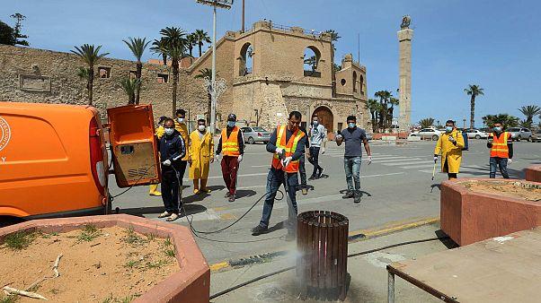 عمال ليبيون يقومون بتطهير شارع في وسط العاصمة طرابلس، 1 أبريل 2020
