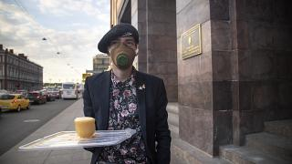 A protester holds a symbolic cup of tea to support Russian opposition leader Alexei Navalny in front of the FSB building  in St. Petersburg, Russia, Thursday, Aug. 20, 2020.