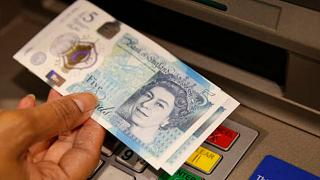 a member of staff at a branch of Halifax bank, in London, displays a new British 5 pound sterling note, made from polymer, which is being launched Tuesday, Sept, 13, 2016