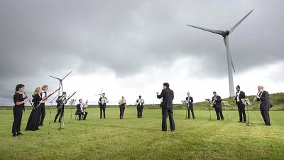 Orchestra for the Earth performs under wind turbines in Delabole, UK.