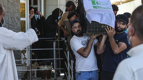 مشيعون يحملون نعش ريهام يعقوب المغطى بالعلم خلال جنازتها في البصرة، العراق