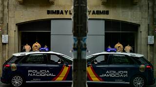 A Spanish police car is reflected in glass during a patrol in Pamplona, northern Spain.