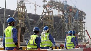 Workers walk to the Lusail Stadium, one of the 2022 World Cup stadiums, in Lusail, Qatar, Friday, Dec. 20, 2019.
