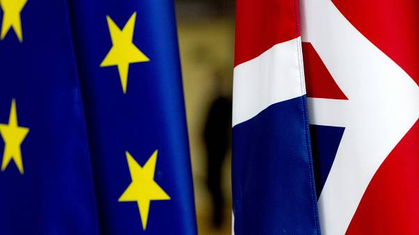 In this file photo dated Tuesday, January 28, 2020, the EU and UK flags are seen inside the atrium at the Europa building in Brussels.