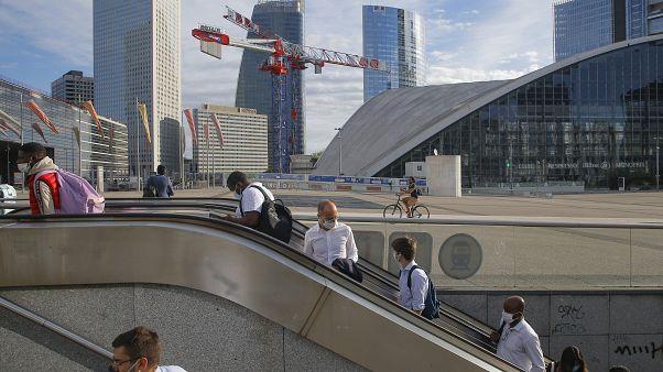 """Usarios del metro salen de la estación con las mascarillas puestas en el barrio parisino de """"La Defense"""""""