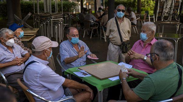 متقاعدون يرتدون كمامات ويلعبون الورق في حديقة في جزيرة جران كناريا في إسبانيا