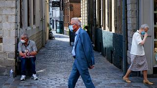 People wearing a protective face masks as a precaution against the coronavirus are seen in a street of Lille, northern France, Friday, Aug. 21, 2020