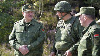Belarusian President Alexander Lukashenko, left, speaks to high rank officers as he visits a military exercise near Grodno, Belarus.
