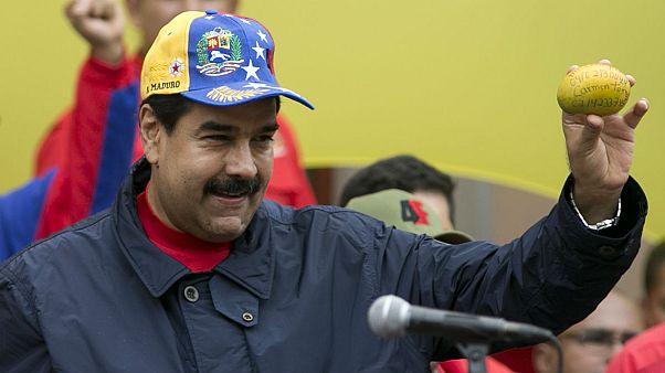 Venezuela's President Nicolas Maduro shows a mango