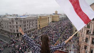 Una mujer ondea una bandera durante la marcha de la oposición en Minsk, Bielorrusia