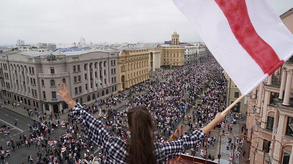 Eine Frau protestiert mit der alten belarussischen Nationalflagge auf einem Dach am Unabhängigkeitsplatz in Minsk