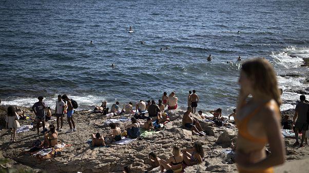 Gente disfruta del sol en la playa de Malmousque de Marsella