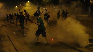 PSG supporters run through tear gas deployed by police forces on the Champs-Élysées after the Champions League final