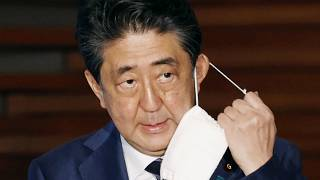 In this May 21, 2020, file photo, Japan's Prime Minister Shinzo Abe removes a face mask as he speaks at a press conference in Tokyo.
