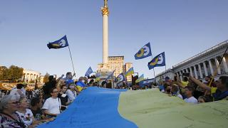 People carry a huge 33 meter-long Ukrainian national flag as they mark the State Flag Day in Kyiv, Ukraine, Sunday, Aug. 23, 2020.