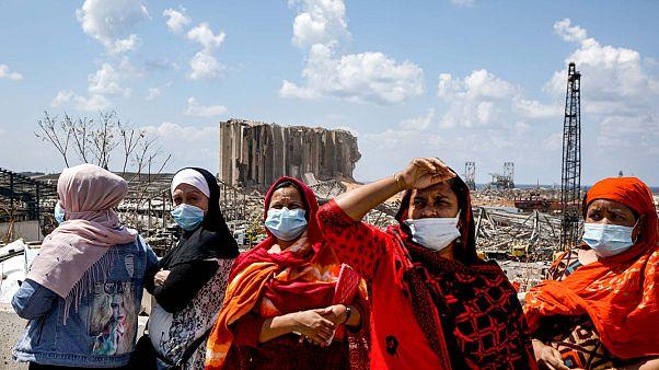 نساء لبنانيات (يسار) وعاملات أجنبيات من جنوب آسيا (يمين) يقفن أمام ميناء العاصمة اللبنانية بيروت المدمر، 9 أغسطس 2020