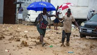 A woman is helped by a man to cross a flooded street during the passing of Tropical Storm Laura in Port-au-Prince, Haiti, Sunday, Aug. 23, 2020.