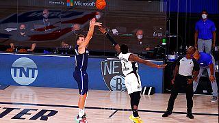 Dallas Mavericks' Luka Doncic, left, hits a winning three-point basket against Los Angeles Clippers' Reggie Jackson.