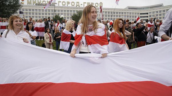 Fehér-piros-fehér nemezti színeket viselő tüntetők Minszkben 2020.augusztus 23-án