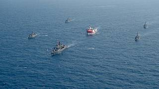 In this photo taken Monday, Aug. 10, 2020, Turkey's research vessel, Oruc Reis, center, is surrounded by Turkish navy vessels as it was heading in the west of Antalya.