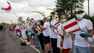 """People hold hands, historical white-red-white flags of Belarus and flowers as they participate in a """"Freedom Way"""""""