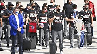 Bavaria Governor Markus Soeder, left, stands with the FC Bayern Munich team after their arrival at Munich Airport, Germany.