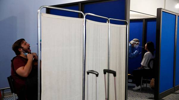 Medical staff conduct a test for the new coronavirus on passengers at Athens Aiport (File Photo)
