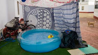 A rubber duck floats in a portable plastic pool that sits in the community housing association patio in Seville, Spain
