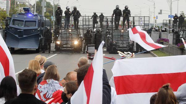 Belorusz tüntetők állnak egy rohamrendőri útlezárással előtt Minszkben 2020. augusztus 23-án