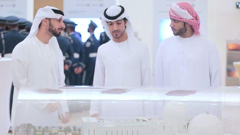 Emirati nationals admire a miniature model of the Barakah plant
