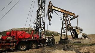 Syrian workers fixing pipes of an oil well at an oil field controlled by a U.S-backed Kurdish group