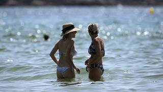 Beachgoers enjoy a hot day in the sun at a beach in Bormes-les-Mimosas, southern France, Tuesday, Aug 11, 2020