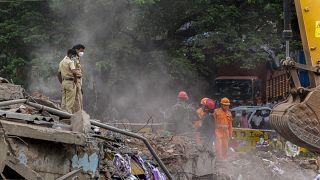 Policías y miembros del equipo de rescate caminan sobre los escombros del edificio derrumbado