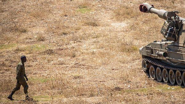 Un soldato israeliano cammina verso un carro armato vicino al confine con il Libano