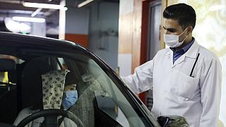 A woman wearing a protective face mask to help prevent spread of the coronavirus has her temperature checked as she enters a shopping center, in Tehran, Iran
