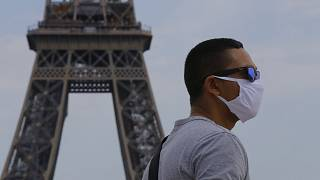 A man wearing a mask to prevent the spread of COVID-19 walks at Trocadero plaza near Eiffel Tower in Paris