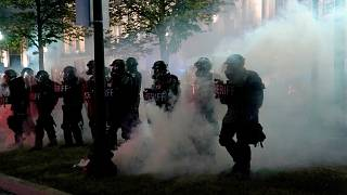 Police clear a park during clashes with protesters outside the Kenosha County Courthouse late Tuesday, Aug. 25