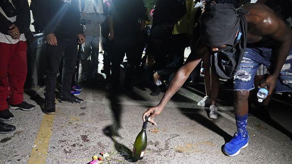 Un manifestant place une bouteille à l'endroit où un homme a été tué par balle mardi soir, lors de manifestations, à Kenosha, États-Unis, le 26 août 2020