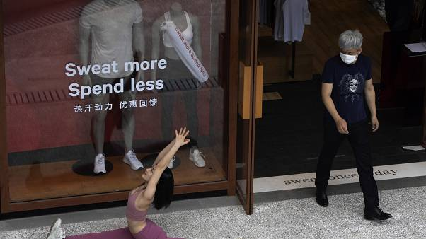 Egy pekingi sportboltból maszkban lép ki egy férfi, miközben maszk nélkül jógázik a bejáratnál egy nő