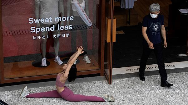 A man wearing a mask to curb the spread of the coronavirus walks past a woman doing a yoga pose for photos in Beijing on Thursday, July 2, 2020
