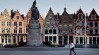 A woman wears a mouth mask as she walks in the Market Square in Bruges, Belgium.