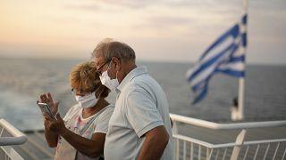 Ένα ζευγάρι φοράει μάσκες και ταξιδεύει με πλοίο