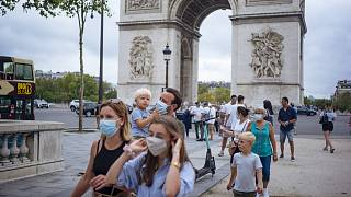 a family wearing protective face masks walk along on the Champs Elysee in Paris.