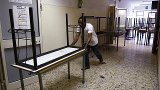 A worker pushes away the old double desks to be substituted by the new single ones for the start of the new school year, at the Isacco Newton high school institute in Rome Wed
